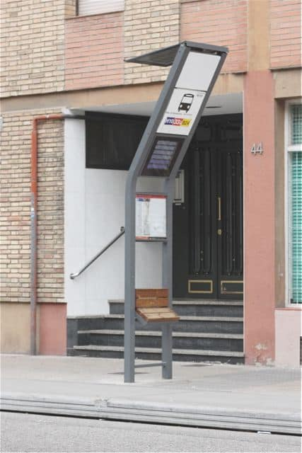 Smart bus stop: solar panel, arrival times, and seat.